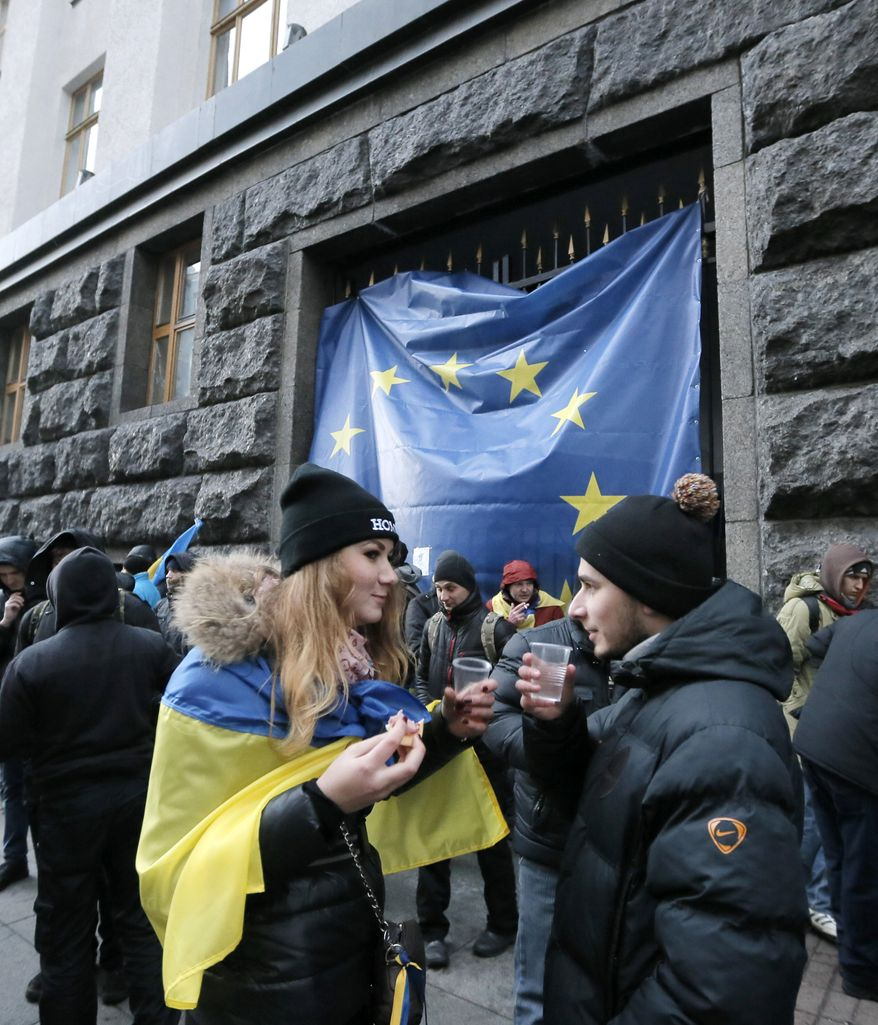 Protesters, one of them covered with a Ukrainian national flag, have tea as they gather for a rally in front of the Cabinet of Ministers its entrance covered with a huge EU flag, in Kiev, Ukraine, Monday, Dec. 2, 2013. Thousands of Ukrainian protesters on Monday besieged government buildings in Kiev and called for the ouster of the prime minister and his Cabinet, as anger at the president's decision to ditch a deal for closer ties with the European Union gripped other parts of the country and threatened his rule. (AP Photo/Efrem Lukatsky)