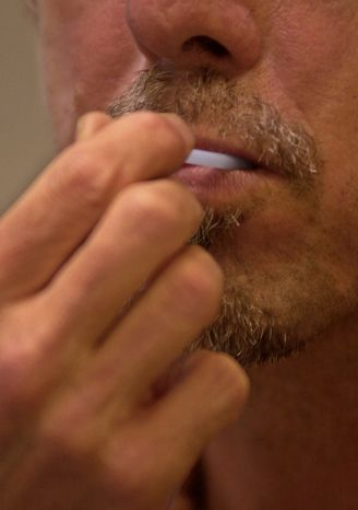 **FILE** A client uses a probe to take a sample from inside his mouth as he takes a free oral HIV test at the Los Angeles Gay & Lesbian Center's HIV testing services center in Los Angeles' Hollywood district on June 21, 2001, that year's national HIV testing day in the United States. (Associated Press)