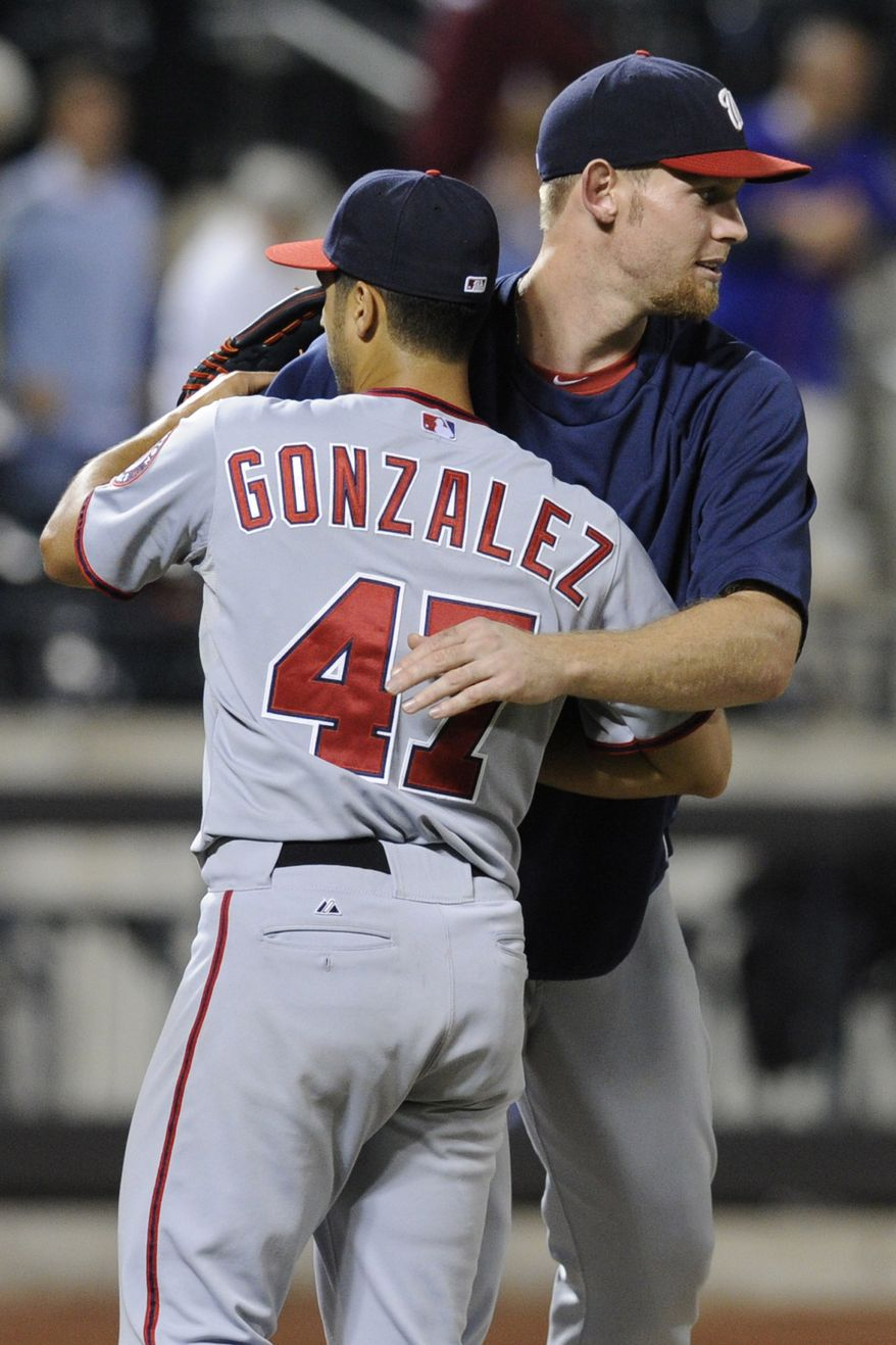 Washington Nationals pitcher Stephen Strasburg, right, hugs Gio Gonzalez after Gonzalez pitched a one-hitter as the Nationals defeated the New York Mets, 9-0, in a baseball game Monday, Sept. 9, 2013, in New York. (AP Photo/Bill Kostroun)