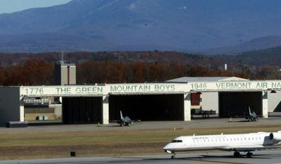 A commercial jetliner taxis past Vermont Air National Guard F-16 fighter jets sitting outside a hangar at Burlington International Airport in South Burlington, Vt., on Monday, Nov. 4, 2013. (AP Photo/Toby Talbot)