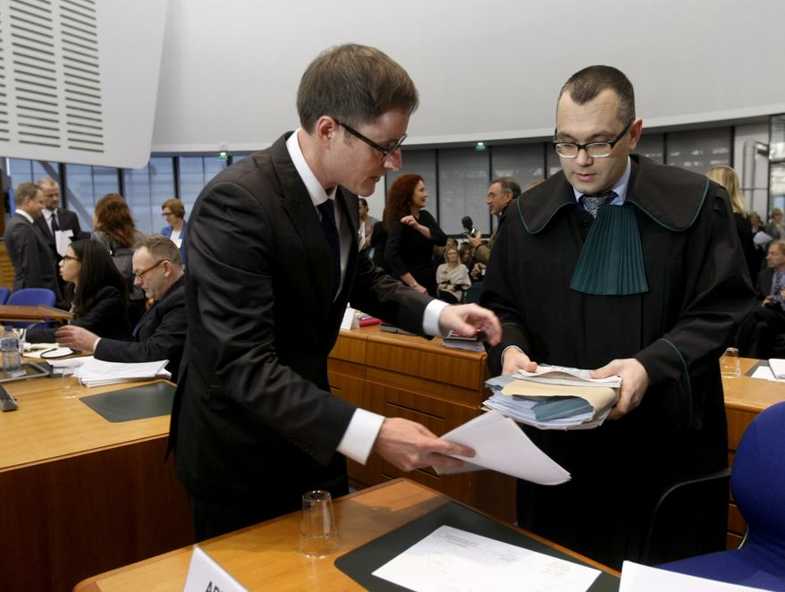 Michael Pietrzak (right), one of the attorneys for Abd al-Rahim al-Nashiri and Abu Zubaydah, is helped by an unidentified assistant as he arrives at the European Court of Human Rights in Strasbourg, France, on Tuesday, Dec. 3, 2013. Lawyers for two terror suspects, currently held by the U.S. in Guantanamo Bay, Cuba, accuse Poland of human rights abuses. (AP Photo/Christian Lutz)