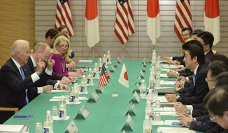 U.S. Vice President Joe Biden, left, gestures during a meeting with Japanese Prime Minister Shinzo Abe, right center, at Abe's official residence in Tokyo Tuesday, Dec. 3, 2013. Biden, who is on the first leg of his three-nation Asian tour, met Abe, whose government is pressing the U.S. to more actively take Japan's side in an escalating dispute over China's new air defense zone above a set of contested islands in the East China Sea. (AP Photo/Toru Yamanaka, Pool)