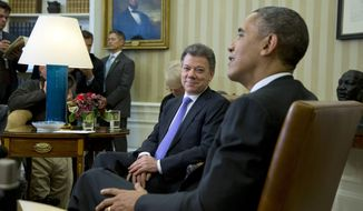 President Barack Obama meets with Colombian President Juan Manuel Santos in the Oval Office of the White House in Washington, Tuesday, Dec. 3, 2013. President Barack Obama says there has been a 20 percent increase in trade between the U.S. and Colombia since the two countries signed a free trade agreement during his first term. The two leaders are holding talks focused on growing the economic relationship between their countries.   (AP Photo/ Evan Vucci)