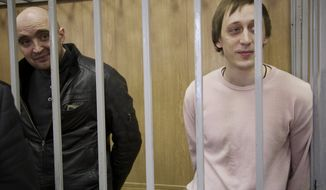 Pavel Dmitrichenko (right), a Bolshoi star dancer on trial over the Jan. 17 acid attack on the Bolshoi Ballet's artistic director, Sergei Filin, and Andrei Lipatov (left) stand in a cage at a courtroom in Moscow on Tuesday, Dec. 3, 2013. (AP Photo/Alexander Zemlianichenko)