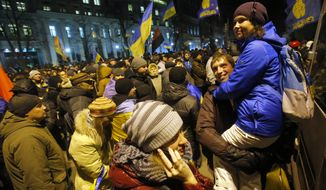 Ukrainians rally outside the presidential administration building in central Kiev on Tuesday, Dec. 3, 2013, after   opposition lawmakers failed to force out the government with a parliamentary no-confidence vote, leaving political tensions unresolved and a potential standoff between protesters and the country's leaders looming. (AP Photo/Sergei Grits)