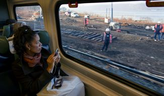 Passengers on a Metro-North train view ongoing repair work near the Spuyten Duyvil station in the Bronx borough of New York Wednesday, Dec. 4, 2013, where a fatal derailment disrupted service on the Hudson Line of the railroad Sunday, Dec. 1. The line was running at ninety eight percent capacity today, according to Metro-North. (AP Photo/Craig Ruttle)