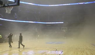 Smoke engulfs the court at The Mexico City arena in Mexico City, Wednesday, Dec. 4, 2013.  The Mexico City arena where the San Antonio Spurs and Minnesota Timberwolves were playing an NBA game Wednesday night was evacuated 45 minutes before tip off because of smoke inside the arena. NBA spokeswoman Sharon Lima says the smoke was coming from a generator fire outside the arena. (AP Photo/Christian Palma)