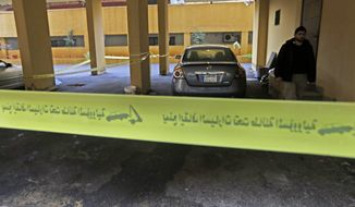 Yellow police tape seals off the scene where Hassan al-Laqis, a senior commander for the Lebanese militant group Hezbollah, was gunned down outside his home, some two miles (three kilometers) southwest of Beirut, Lebanon, Wednesday, Dec. 4, 2013. (AP Photo/Hussein Malla)