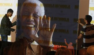 """** FILE ** In this Nov. 2, 2013, file photo, a giant poster of Nelson Mandela is moved to center stage at a news conference held to promote the newly released film """"Mandela: Long Walk To Freedom,"""" in Johannesburg. The ailing former president is not """"doing well"""" but is continuing to put up a courageous fight from his """"deathbed,"""" members of his family have told the South African Broadcasting Corp. in an interview. (AP Photo/Denis Farrell, File)"""