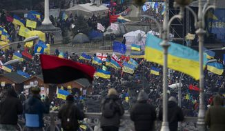 Flags wave over Independence Square during a rally in Kiev, Ukraine, on Wednesday Dec. 4, 2013. A resolution to Ukraine's political turmoil remained elusive as thousands of people continued rallying on Kiev's Independence Square and besieging key government buildings. (AP Photo/Ivan Sekretarev)
