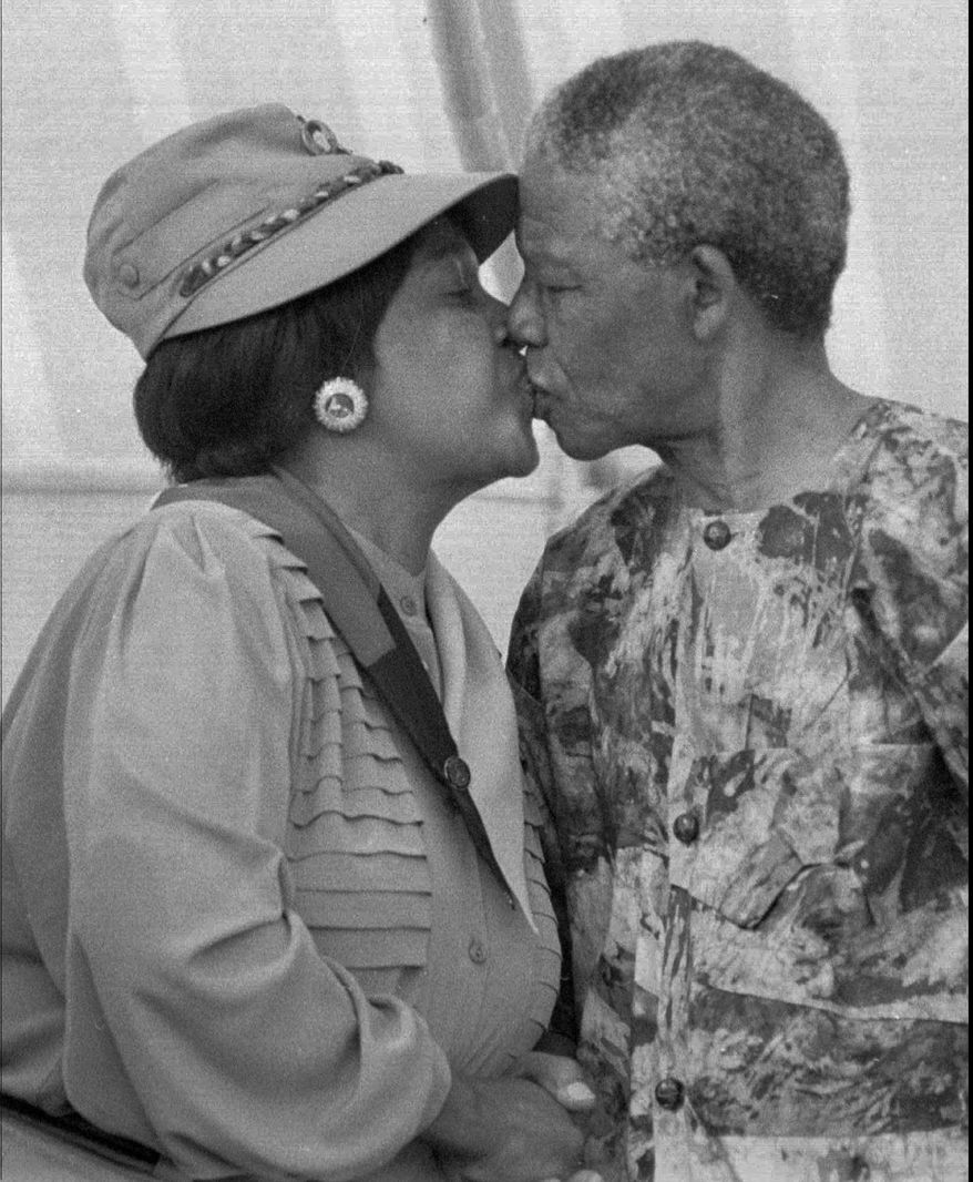 President Nelson Mandela, right, kisses his wife Winnie Mandela at a rally in Cape Town in early 1993. (AP Photo / Benny Gool)