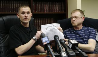 Michael (left) and Eli Hall hold their marriage license certificate on Tuesday, Dec. 3, 2013, as they talk to reporters in Seattle. Michael Hall, a locomotive engineer for BNSF Railway Co., is suing the company for repeatedly denying husband Eli spousal health benefits even though gay marriage is legal in Washington state. (AP Photo/Ted S. Warren)