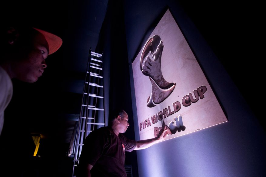 A worker puts the finishing touches to a sign at the entrance for the 2014 soccer World Cup draw in Costa do Sauipe, Brazil,  Thursday, Dec. 5, 2013. The draw for the 2014 World Cup finals takes place Friday, Dec. 6. (AP Photo/Victor R. Caivano)