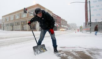 David Velasco shovels snow on a sidewalk in Springfield, Mo., on Thursday, Dec. 5, 2013. Most of southern Missouri was under winter weather warnings, with up to 8 inches of snow possible by Friday evening. (AP Photo/The Springfield News-Leader, Nathan Papes) NO SALES
