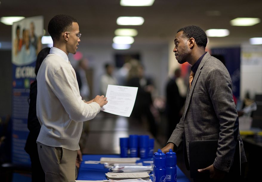 Retired U.S. Air Force Master Sgt. Thomas Gipson (right) of Atlanta has his resume looked over by Ralph Brown, a management and program analyst with the Centers for Disease Control and Prevention, during a job fair for veterans at the Veterans of Foreign Wars Post 2681 in Marietta, Ga., on Thursday, Nov. 14, 2013. (AP Photo/David Goldman)