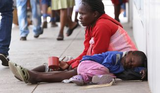 A blind woman begs for money while her child sleeps next to her on the streets of Harare, Zimbabwe, Thursday, Dec. 5, 2013. According to the latest independent surveys in Zimbabwe the gap between the rich and poor continues to grow. The  recent elections in the country have done little to deal with the challenges facing a nation trying to recover from an economic meltdown and the ravages of hyperinflation. (AP Photo/Tsvangirayi Mukwazhi)