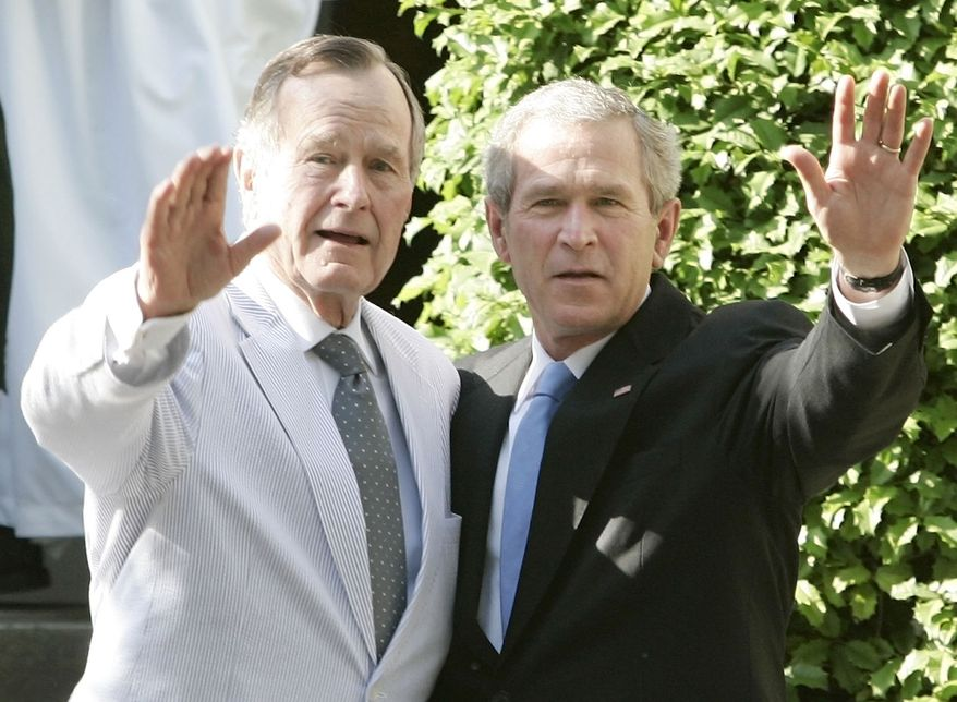 Then-President George W. Bush (right) and his father, former President George H.W. Bush, wave as they leave St. John's Church in Washington on May 6, 2006. (Associated Press) **FILE**