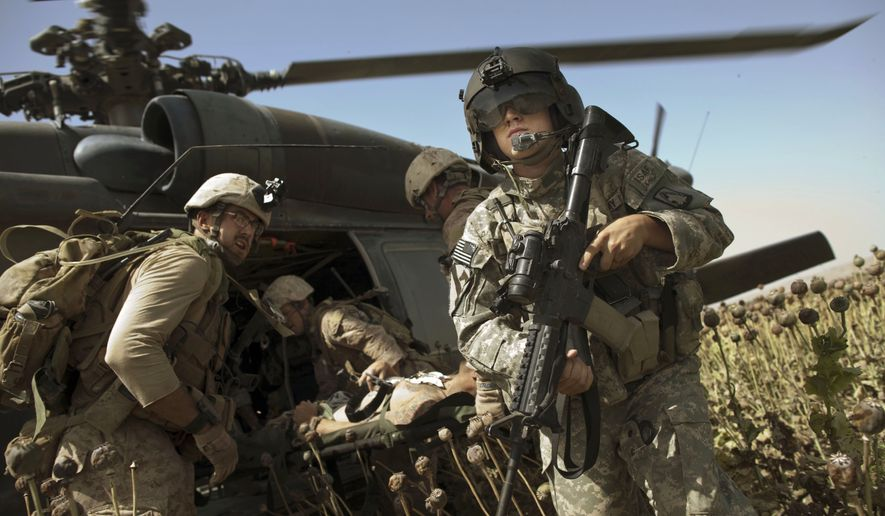 """US Army flight medic SPC. Daniel Miller, right, stands guard as United States Marines place a colleague wounded in an IED strike into a waiting medevac helicopter from the US Army's Task Force Lift """"Dust Off"""", Charlie Company 1-214 Aviation Regiment at a """"hot"""" landing zone in Sangin, in the volatile Helmand Province of southern Afghanistan, Friday, May 13, 2011. (AP Photo/Kevin Frayer)"""