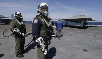 **FILE** Northrop Grumman test pilots Dave Lorenz (right) and Bruce McFadden prepare to taxi the Navy X-47B drone to be launched off the nuclear powered aircraft carrier USS George H. W. Bush off the coast of Virginia on May 14, 2013. (Associated Press)