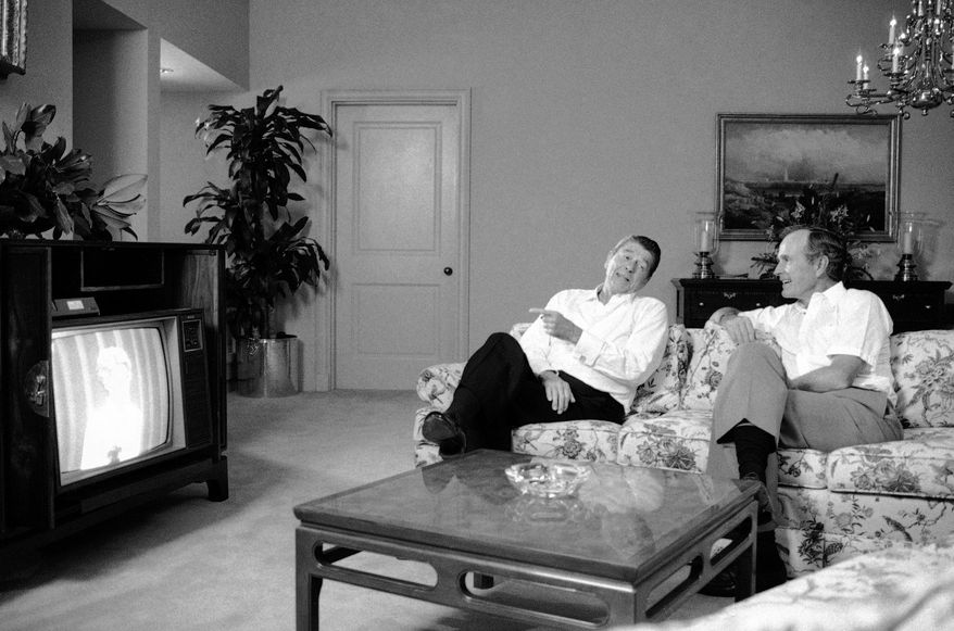 President Ronald Reagan and Vice President George H. Bush sit in the Anatole Hotel at night on Wednesday, August 22, 1984 in Dallas and watch First Lady Nancy Reagan on television as she addresses the Republican National Convention at the Dallas Convention Center.   (AP Photo/J. Scott Applewhite)