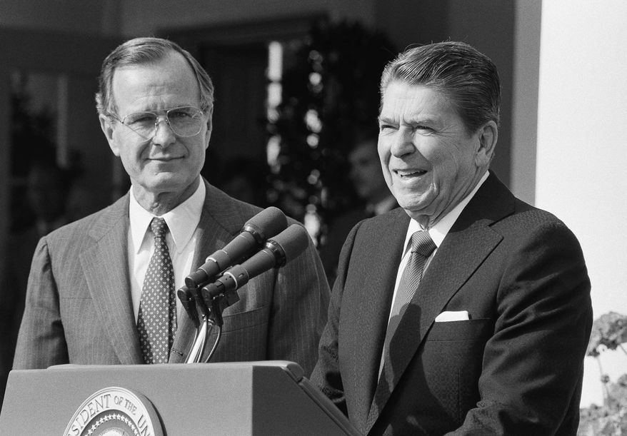 President Ronald Reagan and Vice President George H.W. Bush meet with members of the U.S. Committee on Pacific Economic Cooperation on Tuesday, Sept. 18, 1984 in the White House Rose Garden in Washington. (AP Photo/Barry Thumma)