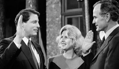 Sen. Albert Gore (D-Tenn.), takes a mock oath of office from Vice President George Bush during a ceremony on Capitol Hill, Jan. 3, 1985.  Gore's wife Tipper watches at center.  (AP Photo/Lana Harris)