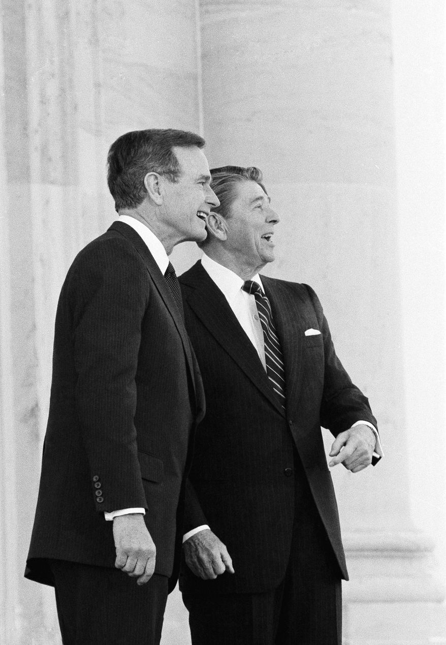President Reagan and Vice President Bush make an appearance on the North Portico of the U.S. Capitol in Washington on Sunday, Jan. 20, 1985 after the President was sworn in for his second term. (AP Photo/Barry Thumma)