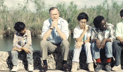 President George H. Bush could pass for just another school boy with the expression he wears as he and a group of school kids listen to Everglade Park Rangers talk about the Florida Everglades on Friday afternoon, Jan. 19, 1990 in the National Park.  The President was in Florida to attend a fund raising dinner for Gov. Bob Martinez. (AP Photo/Ron Edmonds)