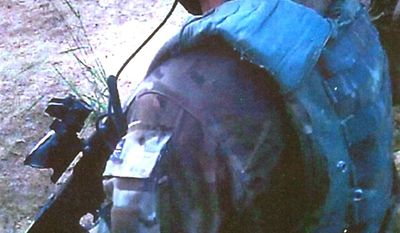 **FILE** In this undated photo, footage captured by a camera mounted on the helmet of a Royal Marine during a patrol in Afghanistan in which an insurgent was murdered in September 2011. A Royal Marine, known as Marine A, was convicted Nov. 8, 2013, by a court martial board of that murder partly on the evidence inadvertently recorded by another soldier only identified as Soldier B. Marine A shot the injured Afghan national, who had attacked his base, in the chest at close range with a 9mm pistol before quoting a phrase from Shakespeare as the man convulsed and died in front of him. (Associated Press/Ministry of Defence)