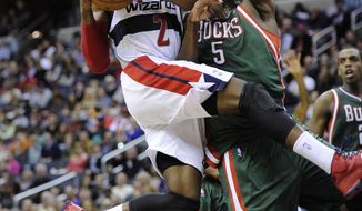 Washington Wizards guard John Wall (2) goes to the basket against Milwaukee Bucks forward Ekpe Udoh (5) during the second half of an NBA basketball game on Friday, Dec. 6, 2013, in Washington. The Bucks won 109-105 in overtime. (AP Photo/Nick Wass)