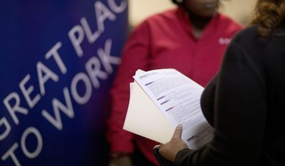 ** FILE ** In this  Thursday, Nov. 14, 2013, file photo, Jimmetta Smith, of Lithonia, Ga., right, the wife of a U.S. Marine veteran, holds her resume while talking with Rhonda Knight, a senior recruiter for Delta airlines, at a job fair for veterans and family members at the VFW Post 2681, in Marietta, Ga. The Labor Department issues the November jobs report on Friday, Dec. 6, 2013.  (AP Photo/David Goldman, File)