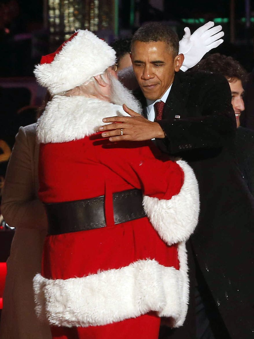 President Barack Obama hugs Santa at the National Christmas Tree lighting ceremony across from the White House in Washington, Friday, Dec. 6, 2013. (AP Photo/Charles Dharapak)