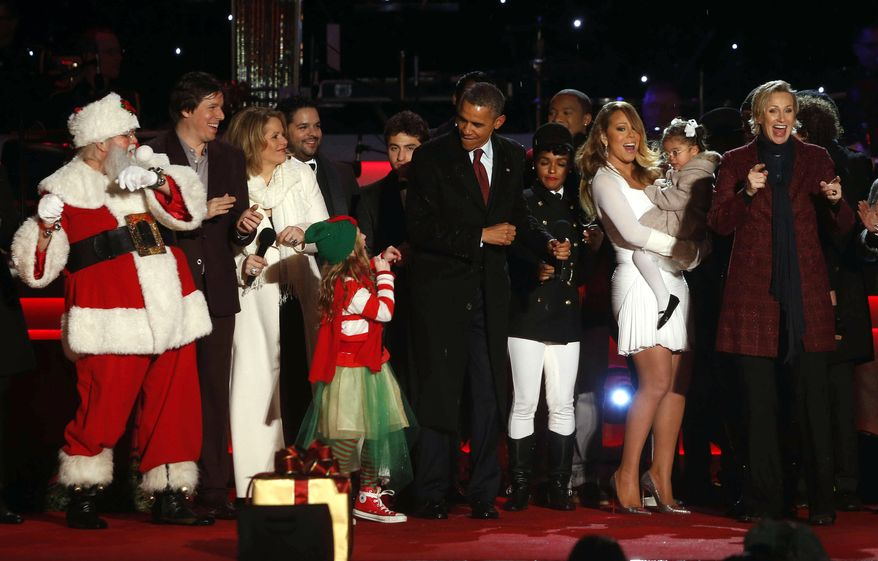 ** FILE ** President Obama dances onstage with members of the cast including Santa, Joshua Bell, Renee Fleming, Mariah Carey, in white, and actress Jane Lynch at the National Christmas Tree lighting ceremony across from the White House in Washington, Dec. 6, 2013. (AP Photo/Charles Dharapak)
