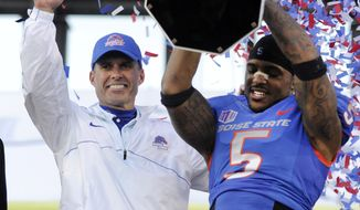 FILE - In this Dec. 22, 2012 file photo, Boise State coach Chris Peterson, left, gestures as cornerback Jamar Taylor holds the championship trophy after the MAACO Bowl NCAA college football game against Washington, in Las Vegas. A person familiar with the decision tells The Associated Press that Petersen has agreed to leave Boise State and be the football coach at Washington.  The person told spoke on the condition of anonymity Friday morning, Dec. 6, 2013,  because the hiring had not been announced by Washington.  (AP Photo/David Becker)