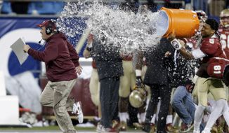 Florida State head coach Jimbo Fisher, left, runs as he is dunked by Jameis Winston, right, as he laughs in the second half of the Atlantic Coast Conference Championship NCAA football game against Duke in Charlotte, N.C., Saturday, Dec. 7, 2013. Florida State won 44-7.  (AP Photo/Chuck Burton)