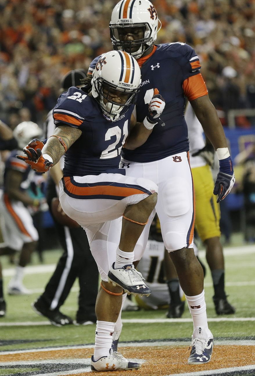 Auburn running back Tre Mason (21) celebrates bios touchdown against Missouri during the second half of the Southeastern Conference NCAA football championship game, Saturday, Dec. 7, 2013, in Atlanta. (AP Photo/Dave Martin)
