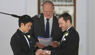 Same sex celebrant Rodger Munson, center, watches Chris Teoh, left, put a wedding ring on Ivan Hinton's finger as they take their vows during a ceremony at Old Parliament House in Canberra, Australia, Saturday, Dec. 7, 2013. (AP Photo/Rob Griffith)