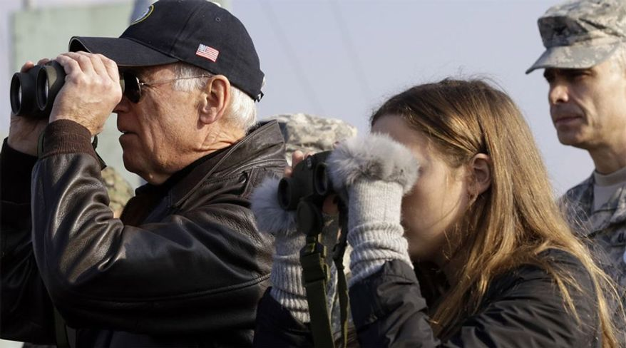 U.S. Vice President Joe Biden, left, looks through binoculars to see North Korea with his granddaughter Finnegan Biden from Observation Post Ouellette during a tour of the Demilitarized Zone (DMZ), near the border village of Panmunjom, which has separated the two Koreas since the Korean War, South Korea, Saturday, Dec. 7, 2013. (Associated Press)