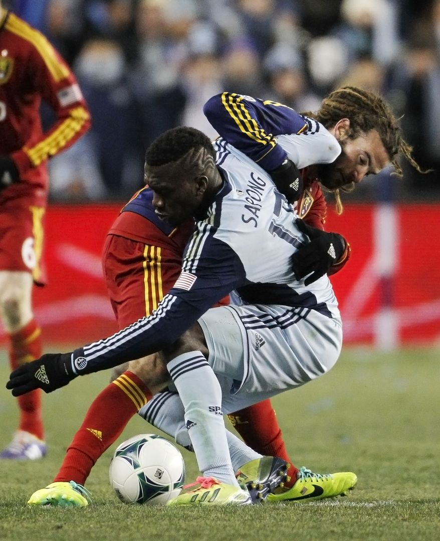 Real Salt Lake midfielder Kyle Beckerman, back, and Sporting Kansas City forward C.J. Sapong, front, battle to control the ball during the second half of the MLS Cup final soccer match in Kansas City, Kan., Saturday, Dec. 7, 2013. (AP Photo/Colin E. Braley)