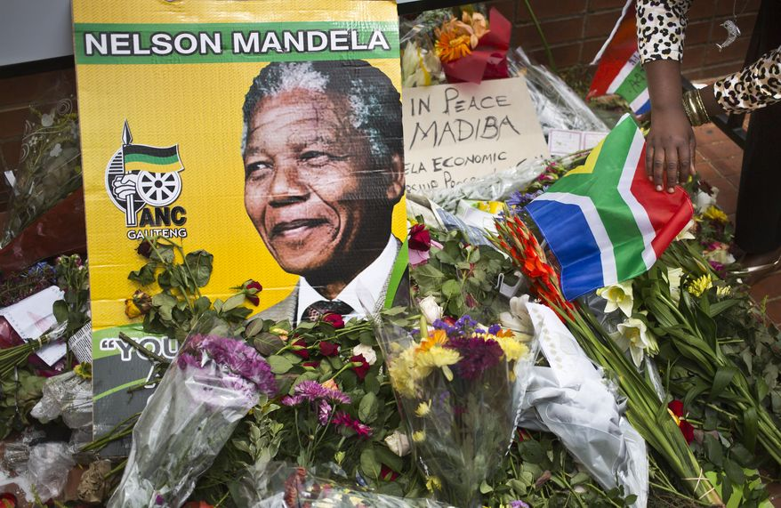 Flowers, posters, and messages left by mourners lie in front of Nelson Mandela's old house in Soweto, Johannesburg, South Africa, Saturday, Dec. 7, 2013. South Africa is readying itself for the arrival of a flood of world leaders for the memorial service and funeral of Nelson Mandela as thousands of mourners continued to flock to sites around the country Saturday to pay homage to the freedom struggle icon. (AP Photo/Ben Curtis)