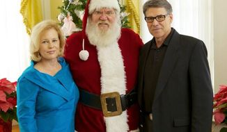 """Texas Gov. Rick Perry, who signed a """"Merry Christmas bill"""" into law, and his wife, Anita, feted a king-sized Santa at the governor's mansion Sunday. (GOv. rick perry)"""