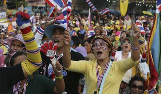 Anti-government protesters shout slogans at the Democracy Monument in Bangkok on Sunday, Dec. 8, 2013. (AP Photo/Manish Swarup)