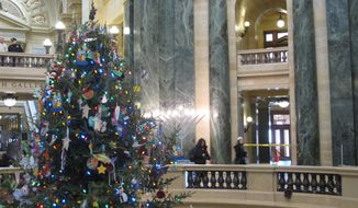 Visitors to the Wisconsin Capitol walk past a menorah and Festivus pole (right) on display in the rotunda, along with a 30-foot Christmas tree, on Thursday, Dec. 5, 2013, in Madison, Wis. The Capitol is full of displays over the holidays, including two traditional Nativity scenes and a sign calling religion nothing but a myth and superstition. (AP Photo/Scott Bauer)