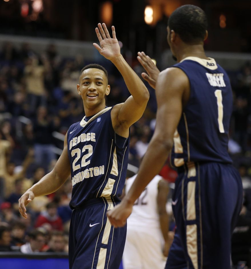 George Washington guards Joe McDonald (22) and Maurice Creek (1) celebrate during a timeout in the first half of an NCAA college basketball game in the BB&T Classic against Maryland, Sunday, Dec. 8, 2013, in Washington. (AP Photo/Alex Brandon)