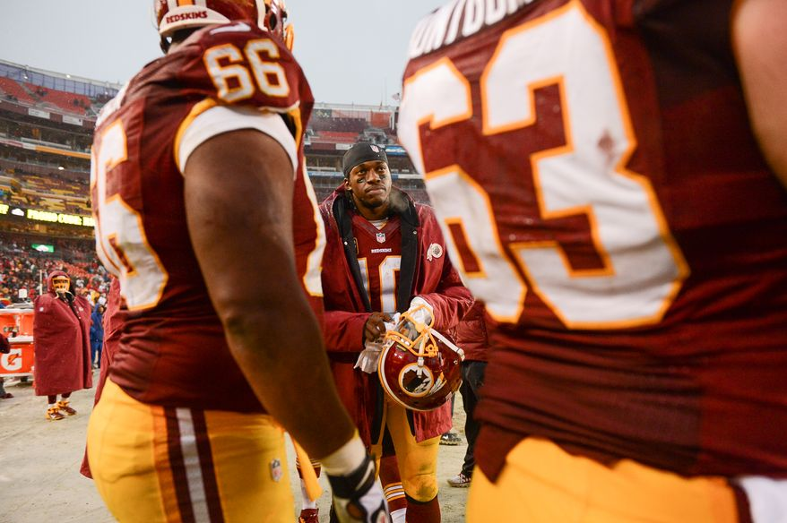 Washington Redskins quarterback Robert Griffin III (10), center, talks with players on the sideline in the fourth quarter after being pulled from the game as the Washington Redskins go on to lose to the Kansas City Chiefs 45-10 at FedExField, Landover, Md., Sunday, December 8, 2013. Also pictured is Washington Redskins running back Alfred Morris (46), center. (Andrew Harnik/The Washington Times)