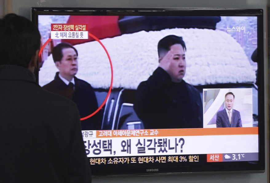 A man at the Seoul Railway Station in Seoul watches a TV news program showing North Korean leader Kim Jong-un (saluting) and Mr. Kim's uncle, Jang Song-thaek (circled), on Tuesday, Dec. 3, 2013. (AP Photo/Ahn Young-joon)