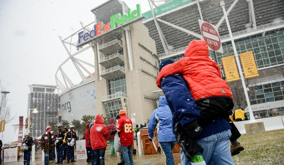 Virgil Cervantes of Vienna, Va., carries his son, Oliver, 9, into FedEx Field as the Washington Redskins get set to play the Kansas City Chiefs in snowy conditions in Landover, Md., on Sunday, Dec. 8, 2013. (Andrew Harnik/The Washington Times)