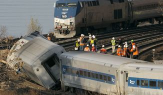 ** FILE ** In this Dec. 1, 2013, file photo, an Amtrak train, top, traveling on an unaffected track, passes a derailed Metro North commuter train in the Bronx borough of New York. A week after four people riding the derailed train died in the accident, two federal lawmakers proposed Sunday, Dec. 8, 2013, that trains nationwide be outfitted with cameras pointed at engineers and at the tracks. (AP Photo/Mark Lennihan, File)