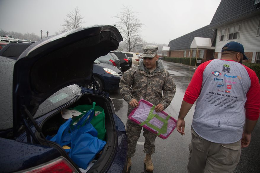 GRATITUDE: Army Spc. Roberto Rodriguez thanks a volunteer for helping him carry bags of food and supplies he received from Operation Homefront on Monday.