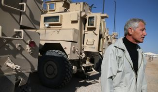 U.S. Secretary of Defense Chuck Hagel, stands in front of MRAP vehicles after speaking with U.S. troops at Camp Bastion, Afghanistan, Sunday, Dec. 8, 2013. Hagel spoke with U.S. troops and thanked them for being deployed for the holidays. (AP Photo/Mark Wilson, Pool)